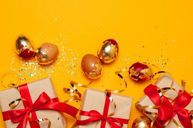 Caixas de presentes do conceito c do feriado de férias e ovos de ouro em um fundo amarelo, vista superior