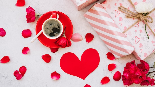 Caixas de presentes em envoltório perto de pétalas de flores, coração de papel e copo com bebida