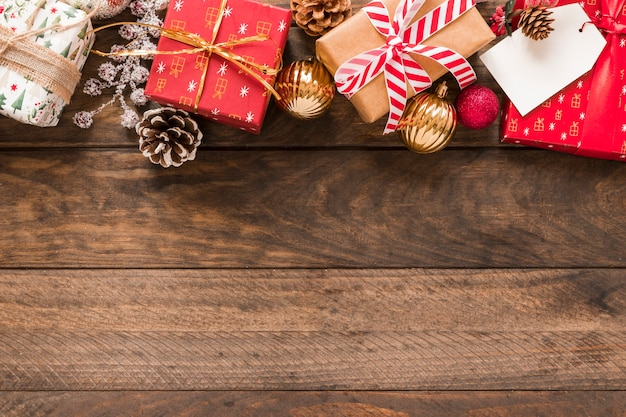 Caixas de presentes em envoltórios de natal com fitas perto de bolas de enfeite