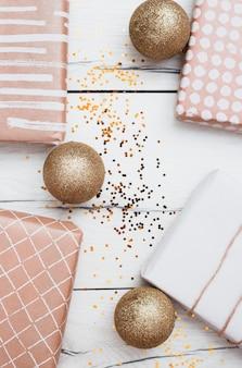 Caixas de presentes em envoltórios perto de bolas de natal