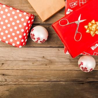 Caixas de presentes em papéis artesanais perto de tesouras e bolas de natal
