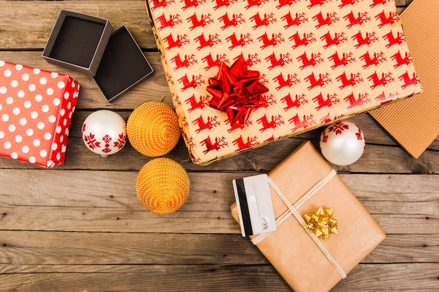 Caixas de presentes em papéis de artesanato perto de cartão de plástico e bolas de natal