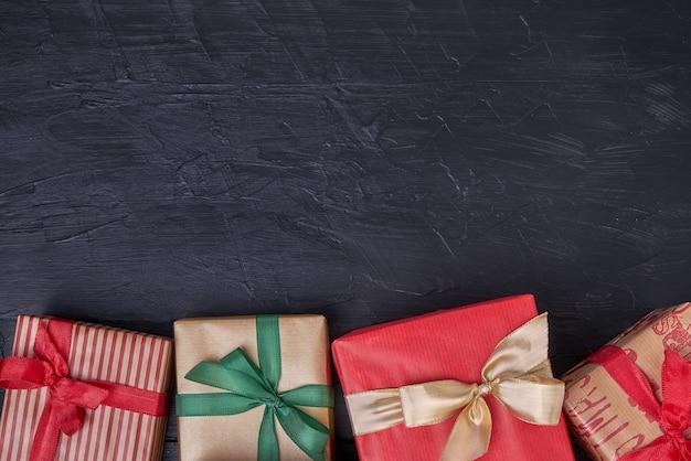 Caixas de presentes embrulhadas decoradas com fita em preto de madeira. copyspace, vista superior