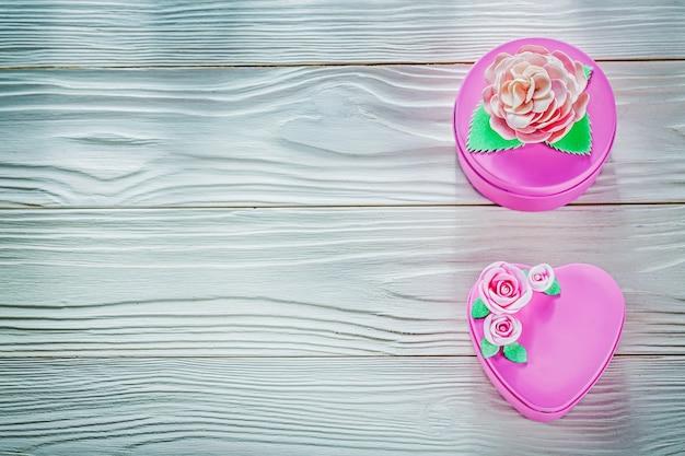 Caixas de presentes embrulhadas em rosa na placa de madeira logo acima da celebração