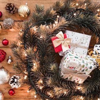 Caixas de presentes entre grinalda de abeto perto de senões e bolas de natal