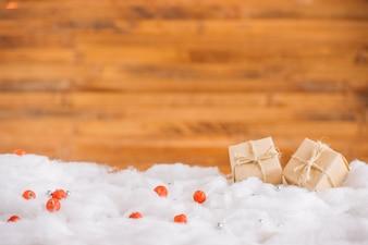 Caixas de presentes na neve decorativa perto da parede