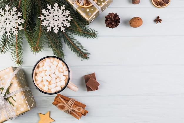 Caixas de presentes no envoltório de natal perto de copo com marshmallows e ramo de abeto