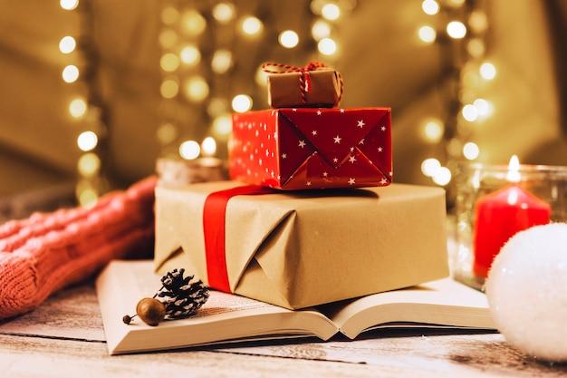 Caixas de presentes no livro perto de vela acesa