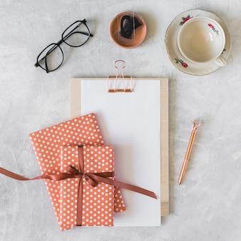 Caixas de presentes, óculos, prancheta e copo