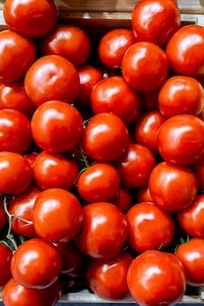 Caixas de tomates vermelhos brilhantes prontos para a venda em um mercado de agricultores
