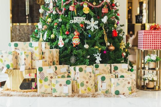 Caixas decoradas com presentes de natal debaixo de uma árvore de natal em casa