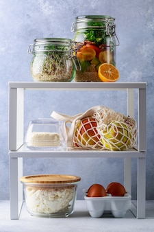 Caixas e latas de vidro com decantação de refrigerador de alimentos frescos