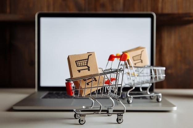 Caixas em carrinhos em um teclado de laptop. conceito de negócio, comércio eletrônico e compras.