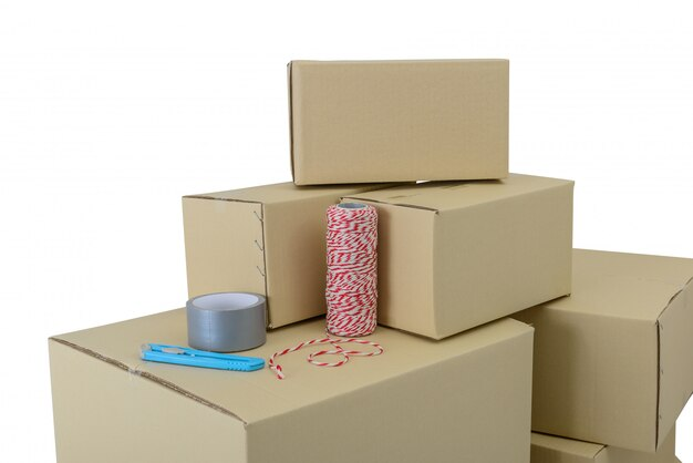 Caixas em tamanhos diferentes, caixas empilhadas, fita adesiva, corda e cortador isolados
