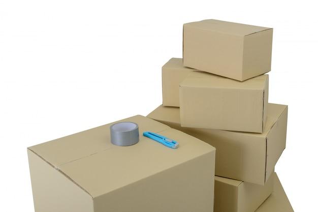 Caixas em tamanhos diferentes, caixas empilhadas, fita adesiva e cortador isolados em background brancos