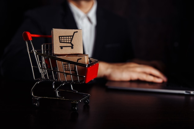 Caixas em um carrinho ao lado do laptop. conceito de compra e entrega online