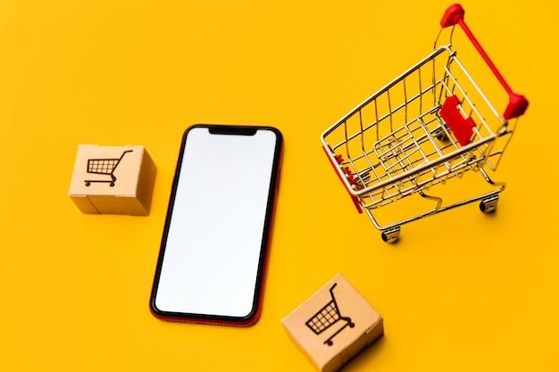 Caixas em um carrinho de compras ou carrinho e smartphone móvel