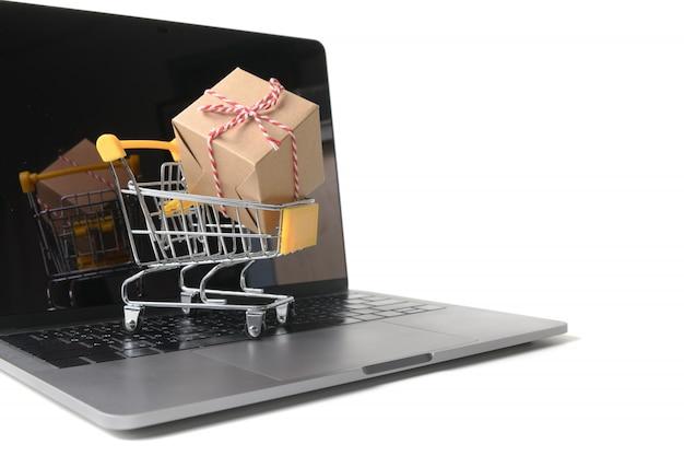 Caixas em um carrinho em um teclado de laptop isolado