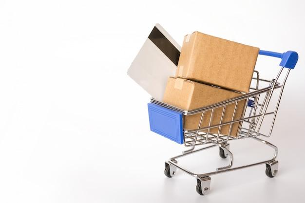 Caixas ou caixas de papel e cartão de crédito no carrinho de compras azul no fundo branco.