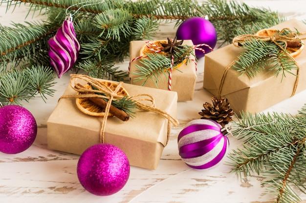 Caixas para presente de ano novo ou natal com as tradicionais decorações orgânicas festivas, feitas com as próprias mãos. ramos de abeto e brinquedos.