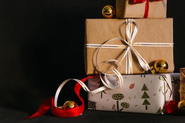 Caixas para presentes embaladas em papel de embrulho e amarradas com fitas para o ano novo ou natal têm um fundo preto, ao lado estão as bolas douradas de natal. se preparando para o feriado.
