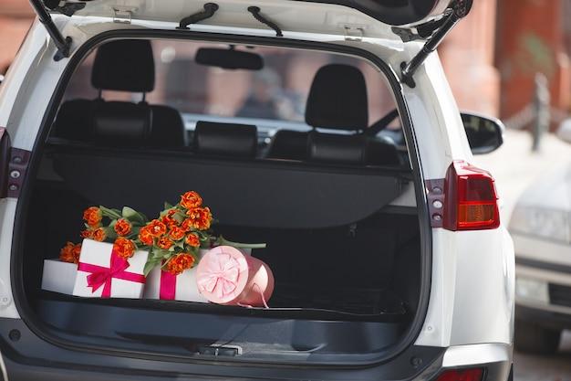 Caixas, presentes, presentes e flores no porta-malas ou bagageira do carro. ainda de automabile com tulipas e presentes no dia das mulheres.