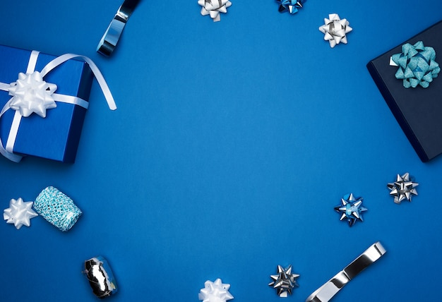 Caixas quadradas de presente de papelão, arcos, fitas para embalagem em um azul escuro