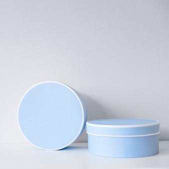 Caixas redondas azuis na mesa branca e fundo branco como presentes ou pacotes