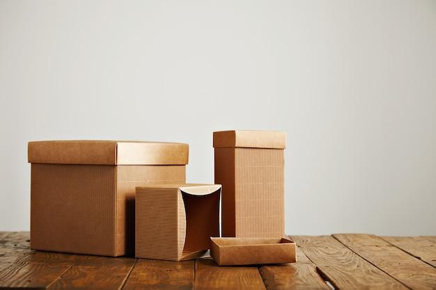 Caixas semelhantes não rotuladas de diferentes formas e tamanhos em uma mesa de madeira irregular isolada no branco