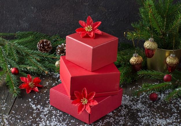 Caixas vermelhas com presentes e no fundo ramos de abeto e decoração festiva