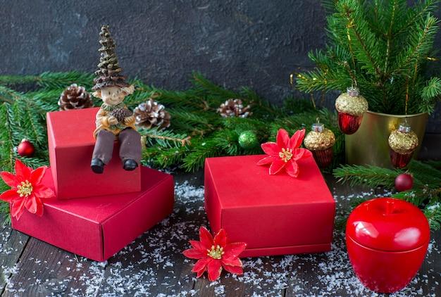 Caixas vermelhas com presentes, maçã decorativa vermelha e gnomo sentado em uma caixa