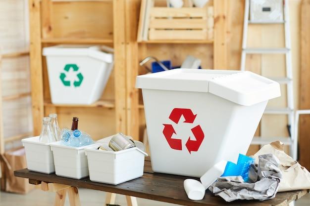 Caixotes de plástico e caixas para diferentes tipos de lixo sobre a mesa, reciclando os resíduos no armazém