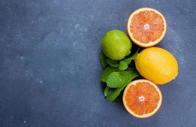 Cal, limão e laranja vermelha no stonebackground azul. ingredientes para mojito ou limonada