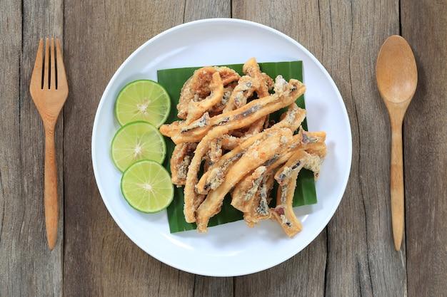 Calamar fritado de mariscos tailandeses no prato branco no assoalho de madeira.