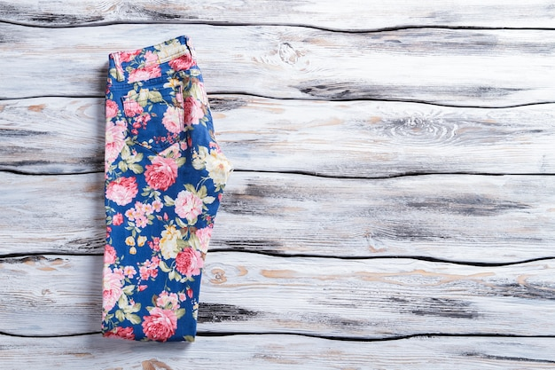 Calça casual com estampa floral calça leve em fundo de madeira calça dobrada deitada na prateleira por último.