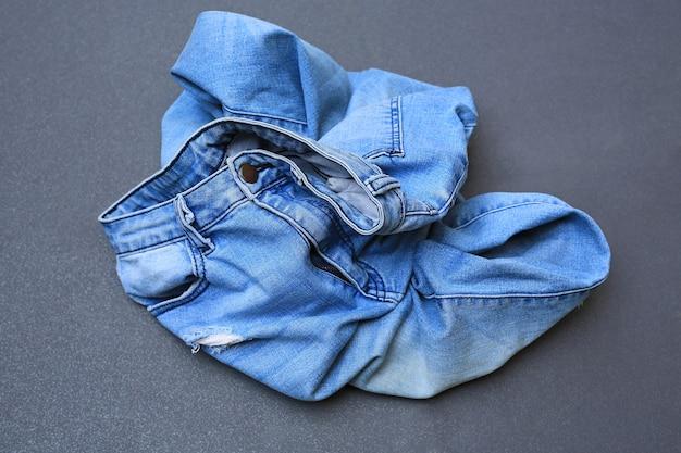 Calça jeans amarrotada no fundo do piso de ladrilho cinza