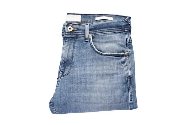 Calça jeans azul dobrada isolada no fundo branco.