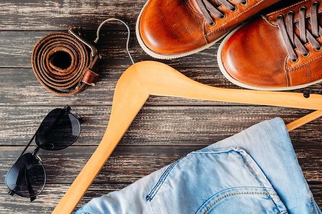 Calça jeans casual de couro marrom no cabide, cinto e óculos de sol