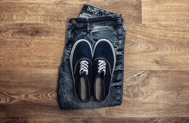 Calça jeans com tênis no chão de madeira. vista do topo