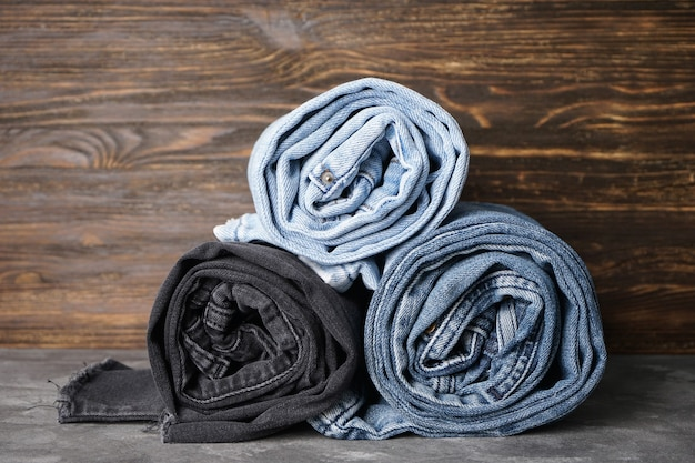 Calça jeans dobrada em rolos sobre fundo cinza e madeira.