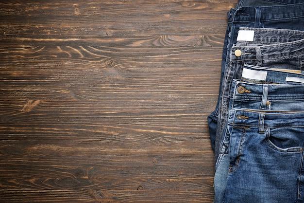 Calça jeans dobrada na mesa de madeira, espaço para texto. postura plana.