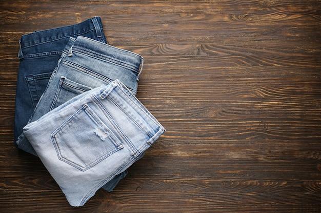 Calça jeans dobrada na mesa de madeira, lugar para texto. vista do topo.
