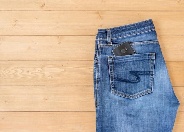 Calça jeans e acessórios masculinos no chão de madeira.