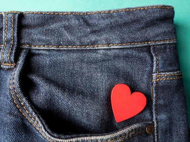 Calça jeans e um coração vermelho estão no bolso de trás da calça jeans verde