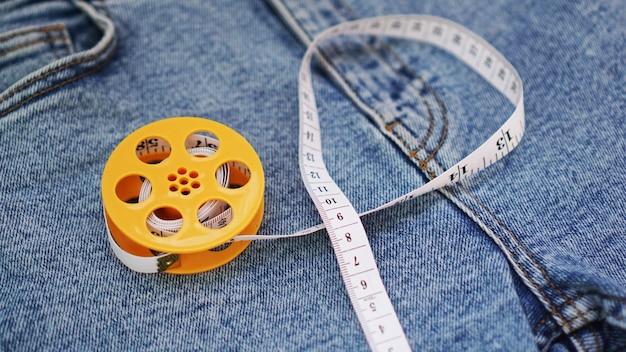Calça jeans e uma fita métrica. conceito de emagrecimento ou costura jeans. fita métrica em carretel amarelo em fundo de jeans