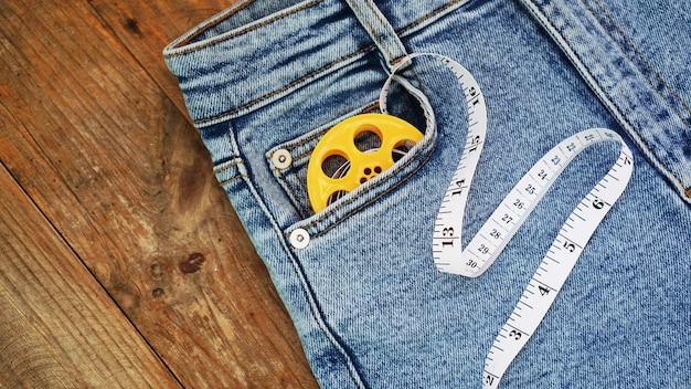 Calça jeans e uma fita métrica. conceito de emagrecimento ou costura jeans. jeans com fundo de madeira
