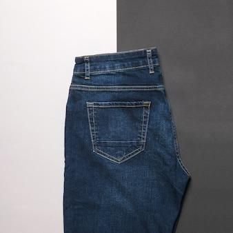 Calça jeans escura masculina em uma superfície preta e branca. jeans e desgaste denim.