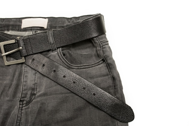 Calça jeans feminina cinza de cintura alta com cinto de couro preto. espaço para texto