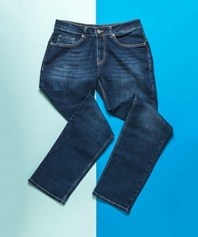 Calça jeans masculina caprichosamente dobrada sobre uma superfície azul claro e escuro. jeans e desgaste denim.