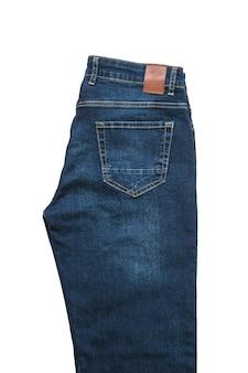 Calça jeans masculina com etiqueta de couro isolada em uma superfície branca. roupas masculinas de jeans da moda. postura plana. a vista do topo.